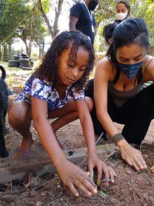 Imagem mostra duas crianças do projeto manejando a terra
